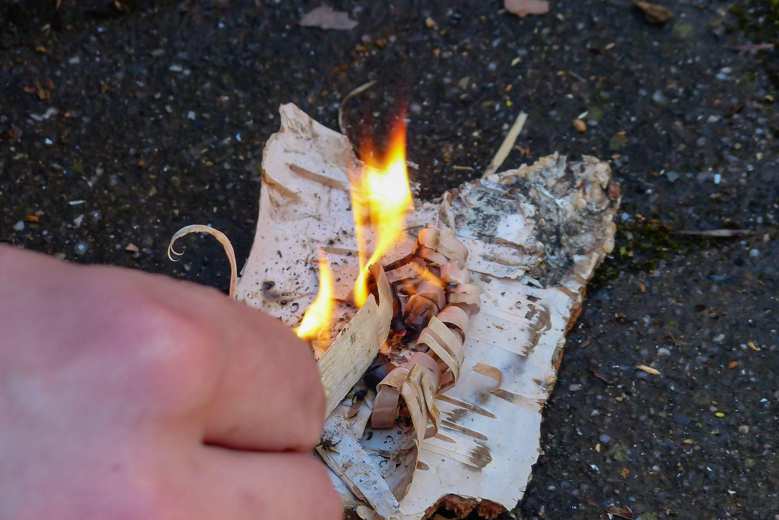 Jemand macht Feuer mithilfe von kleinen Holzspähnen