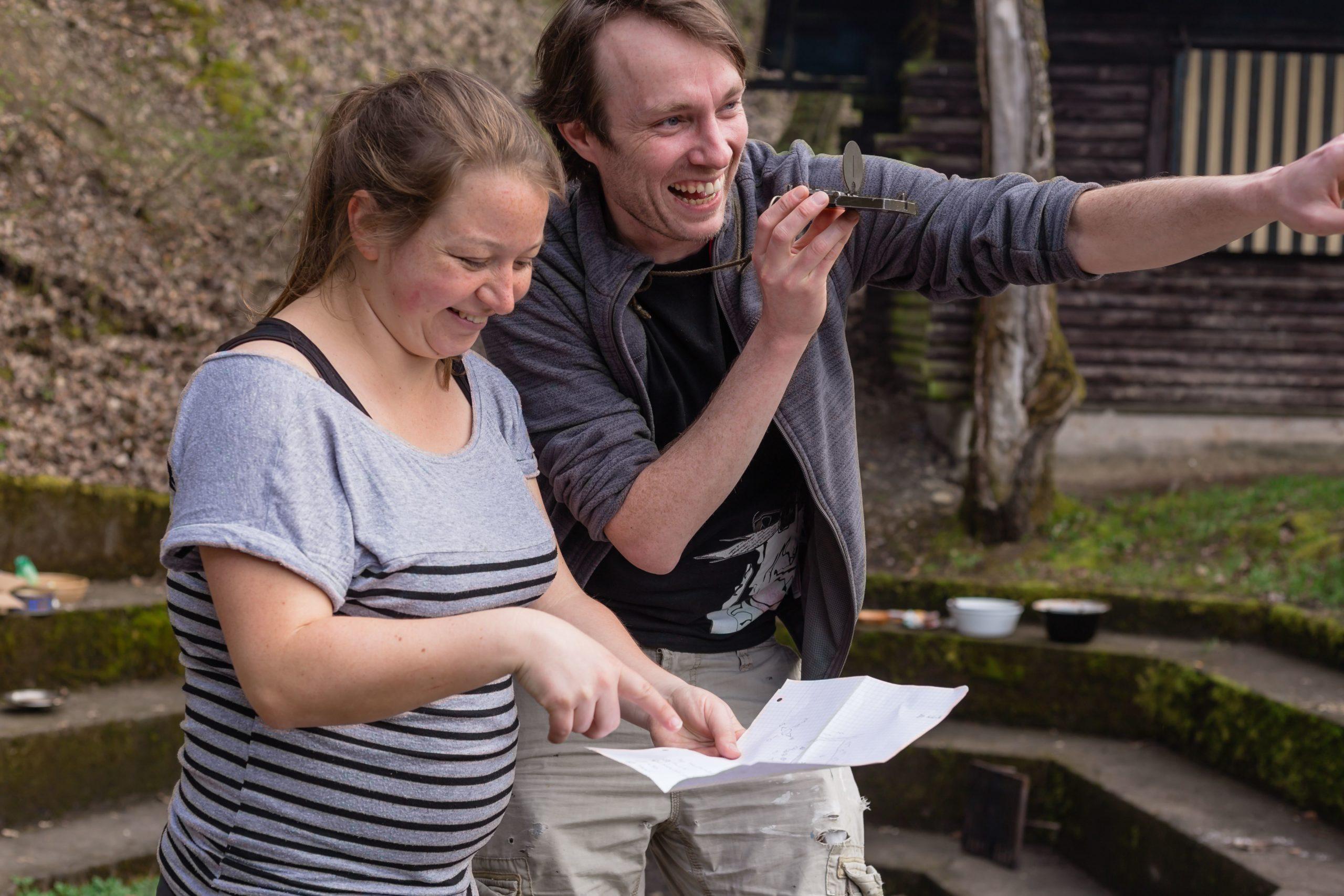 Zwei Personen navigieren mit Hilfe eines Kompasses und einer Karte
