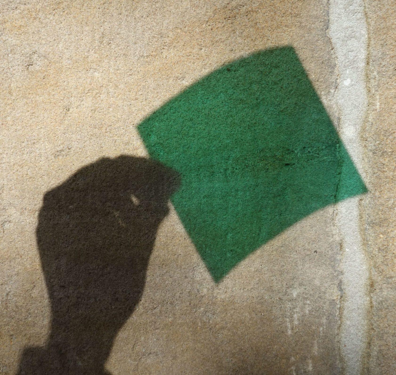 Jemand wirft mit Transparentpapier einen grünen Schatten an eine Wand
