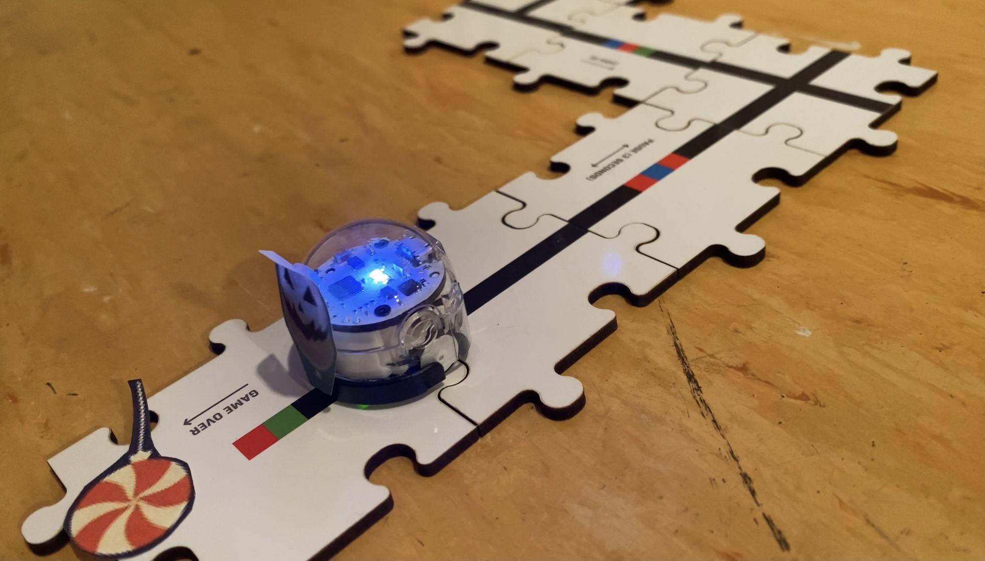 ein kleiner leuchtetender Roboter bewegt sich über eine Strecke